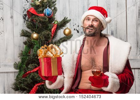 Handsome bad Santa happy smiling and holding gift or present in front of him. Santa Clause drinking delicious wine in studio.