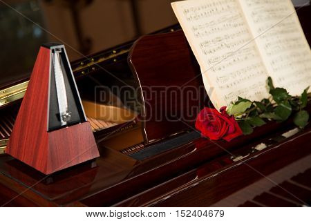 Music Book, Metronome And Red Rose on Piano - Close Up