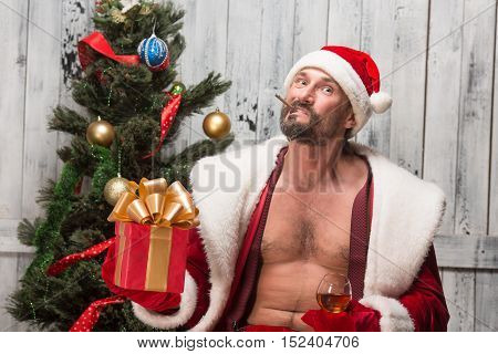 Portrait of bad Santa Clause prefers drinking alcohol drinks and smoking sigars. Bad habits of bad Santa Clause in studio.