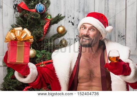 Bad Santa congratulating everybody with New Year holiday while drinking wine, smiling sigars and holding girf or present in studio.