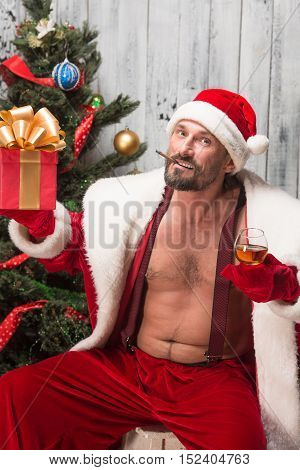 Portrait of sexy Bad Santa Clause congratulating everybody with New Yeat and Christmas holidays while posing for photographer in studio.