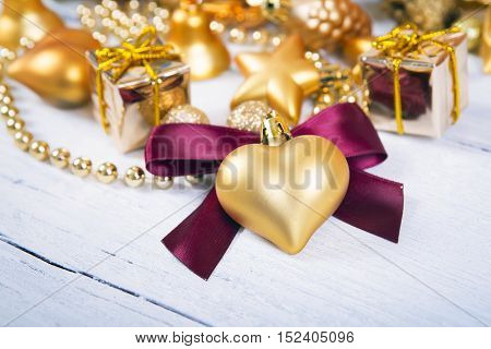 Brilliant gold baubles and cones like christmas decoration. Yellow balls ribbon gift red bow and tinsel isolated on white wooden background.