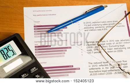 Glasses, Pen And Calculator On Performance Overview Close-up