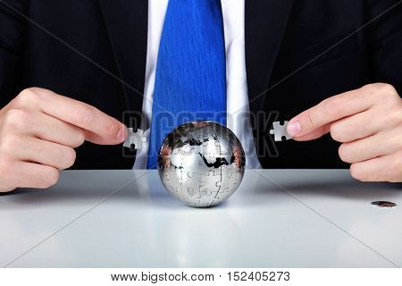 Business man solving a world puzzle - concept of business problems and solutions of a global scale