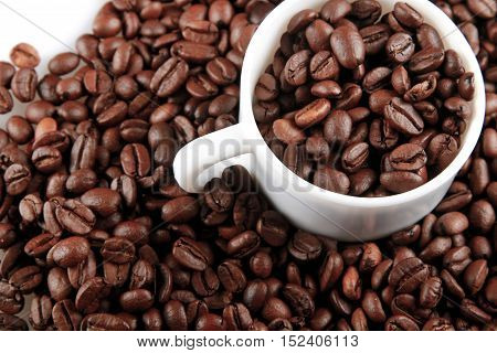 Mug full of, and surrounded by, coffee beans