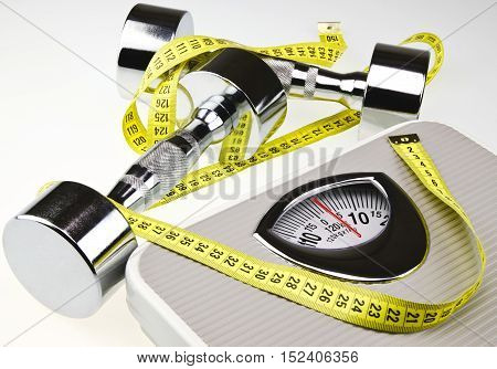 Dumbbells, Weight Scale and Tape Measure on Gray Background