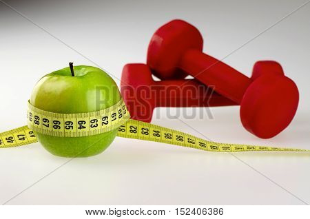 Dumbbells, Apple and Tape Measure on Gray Background