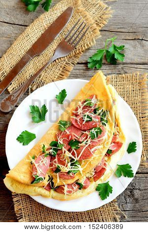 Delicious stuffed omelet on a plate. Stuffed omelet with fried sausages, grated cheese and parsley, fork, knife on an old wooden background. Breakfast recipe with eggs. Top view