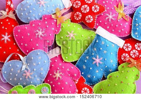 Christmas tree ornaments. Kids winter background. Cute felt Christmas trees, hearts, stars, mittens toys embellished with beads and snowflakes. Top view