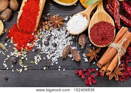 Colorful powder spices on spoons in black wooden table background, top view
