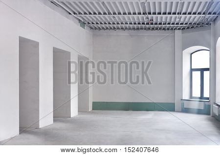 The interior of the reconstructed building. White concrete walls and floor. Metal ceiling on beams.