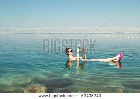 Photo of the Girl reading newspaper floating on surface Dead Sea enjoy summer sun and vacation. Recreation tourism, healthy lifestyle, free time concept