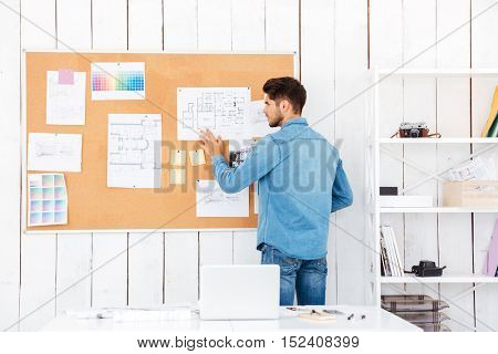 Back view of a casual businessman posting task stickers on board in office