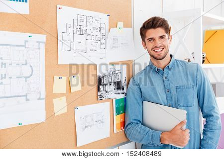 Close up portrait of a smiling man standing at the task board and holding laptop