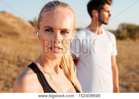 Beautiful young sports couple with earphones standing outdoors