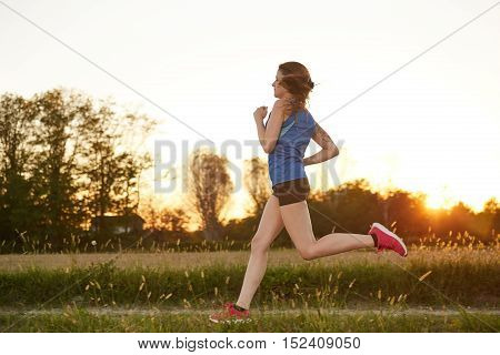 young blond woman running in the fields
