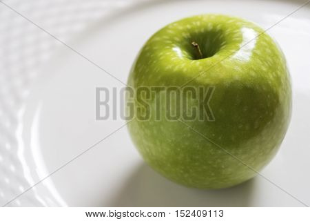Green Apple on the White Plate. Shiny Organic Granny Smith Close Up.