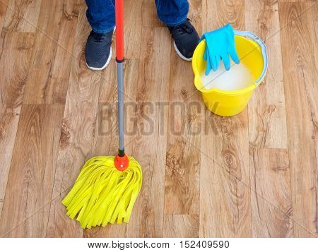 Cleaning a wooden parquet with a mop
