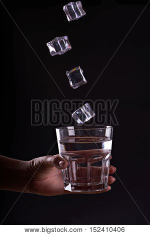 Woman holds a glass of water with ice cubes in motion . Give a glass of water. Drink more wate with icer. Black background.
