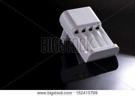 White Battery Charger on Shiny Black Background
