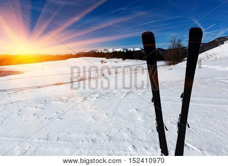 Mountains ski in snow on winter resort against sunset
