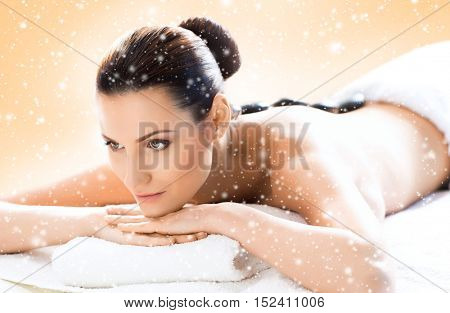 Young and beautiful girl relaxing in Christmas spa salon. Massage therapy, healing medicine and health care concept. Winter background.