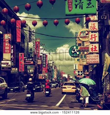 Zhongli District, Taoyuan City - October 2016: Street view with signboards people and traffic in sunny day. Retro look.