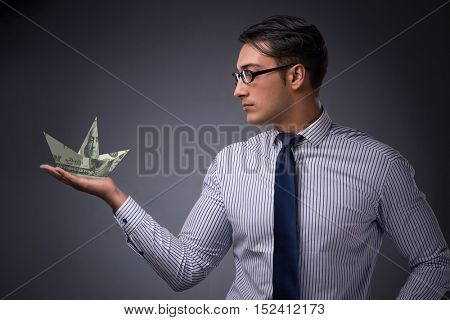 Businessman holding dollar paper boats
