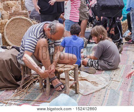 Elderly Man Weaves Chair At The Fair