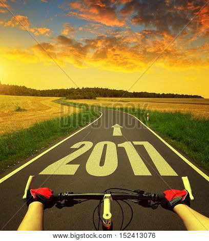 Cyclist riding a bike at sunset. Forward to the New Year 2017