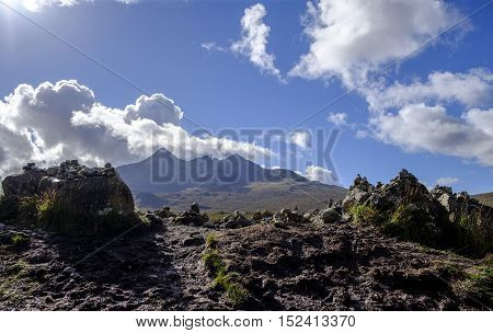 Group of stone cairns with background of mirroring the shapes of the dramatic peaks of the Cuillin mountain range in Isle of Skye Scotland
