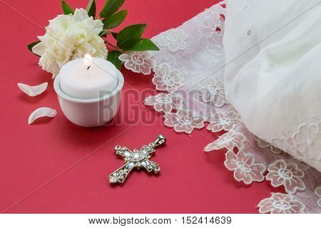 Red christening background with white vintage lace dress candle and christian cross pendant