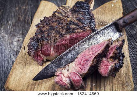 Barbecue Wagyu Tomahawk Steak on old Cutting Board