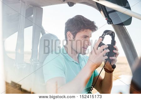 Handsome young man pilot in cabin of small aircraft