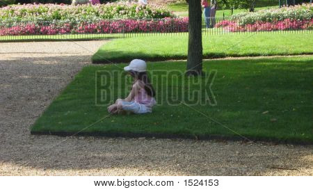 A Girl Sitting Relaxing On The Grass Alone.