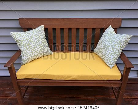 Outdoor wooden bench on a wooden deck by a house.