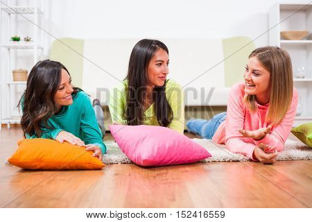 Three friends are having nice time together. They are lying on floor and talking.
