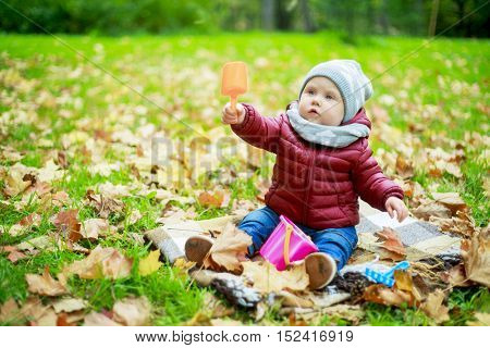 baby girl playing outdoor in the autumn park