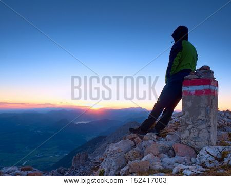 Tired Hiker Sit On Border Stone On Alps Mountain. Austria Germany Border. Daybreak Above Foggy Valle