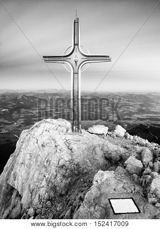 Cross Raised  At Alpine Mountain Peaksharp Rocks, Sun In Sky.