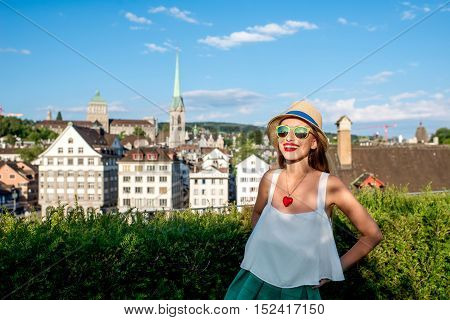 A portrait of a young female tourist on the beautiful old townscape background in Zurich city. Having a happy vacation in Switzerland