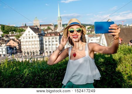 Young female tourist making selfie photo on the beautiful old townscape background in Zurich city. Having a happy vacation in Switzerland