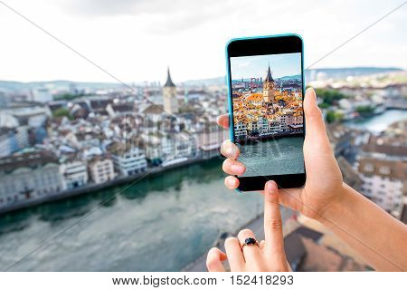 Photographing with smart phone aerial view on Zurich old town in Switzerland