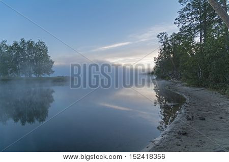 Foggy morning on the river. The fog creeps over the surface of the water. River Chirko-Kem Karelia Russia.