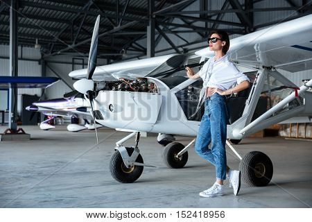 Full length of attractive young woman in sunglasses standing near small aircraft