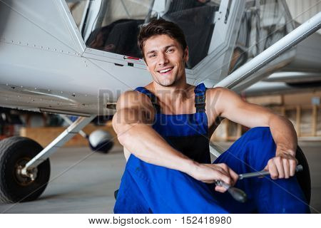 Happy smiling mechanic in overall resting after hard working day holding wrench