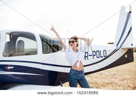 Attractive young woman posing near a plane and pointing finger up outside