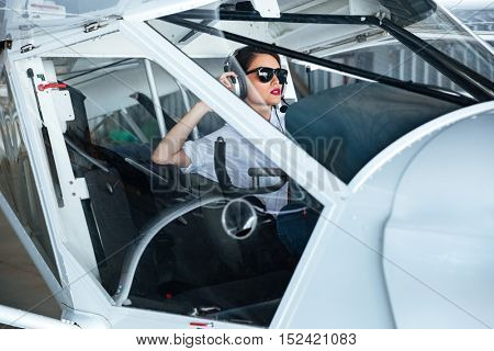 Beautiful young woman pilot in sunglasses and headset sitting in cabin of small aircraft