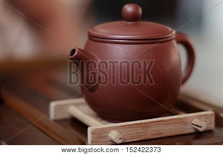 Teapot brewing Chinese tea on a stand