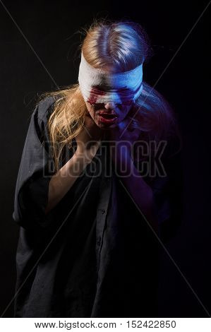 scared bloody girl with bandage on head on black background